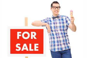 Man holding an ice cream by a for sale sign