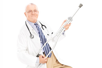 Mature doctor playing guitar on a crutch