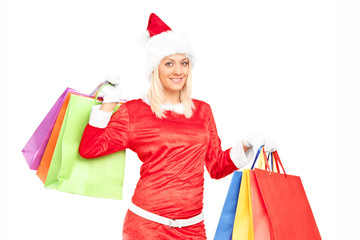 Woman in Santa costume holding bags