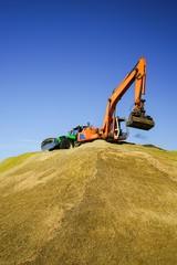 Biogas - Bagger und Traktor plätten hohen Maishaufen