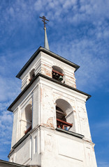 Bellfry of old Russian church against blue sky