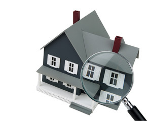 A magnifying glass examining a miniature model home.