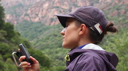Portrait of young woman in the mountains looking at GPS