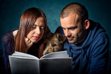 couple and their dog reading a book