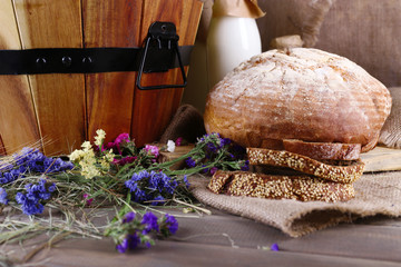 Big wooden basket with dried flowers and milk closeup