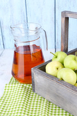 Ripe apples and juice in basket on table close-up