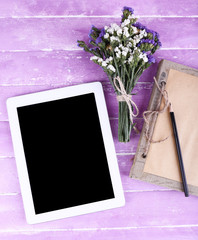 Tablet, notebook, pencil and bunch of field flowers