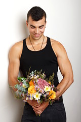 Young man in black undershirt with bouquet of flowers