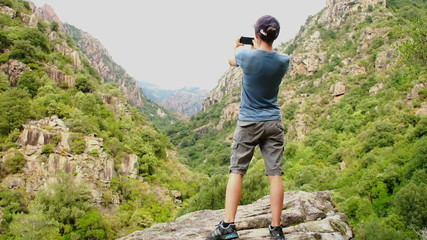 Hiking woman taking photo with smart phone at mountain peak