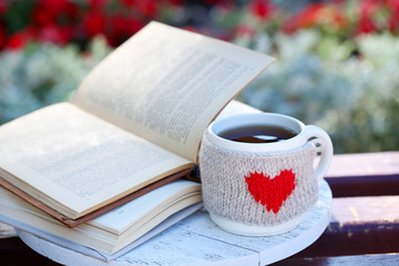 Cup with hot drink and book on bench, outdoors