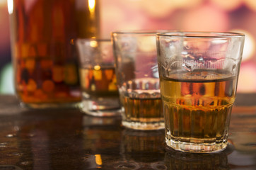shots of rum whiskey over defocused lights background