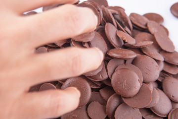 Close up view of hand picking up chocolate button