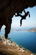Silhouette of a young female rock climber on cliff