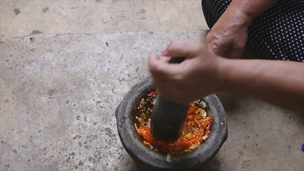 Pounding Thai chili sauce in stone mortar with pestle