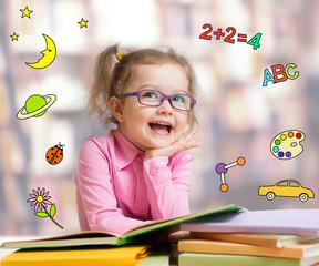 Funny smart kid in glasses reading book