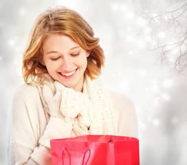 Beautiful young woman looking at a gift bag
