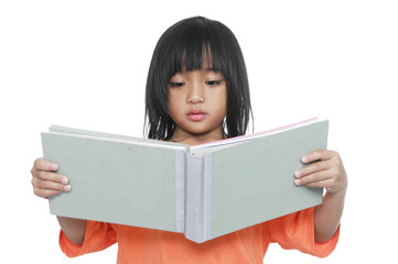 Little girl with large book reading book.