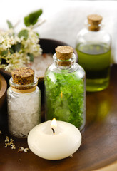 salt in wooden bowl with salt in glass , candle, massage oil