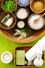 sea salt in wooden bowl with spoon, on soft green towel