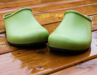 Garden shoes on wet wooden deck