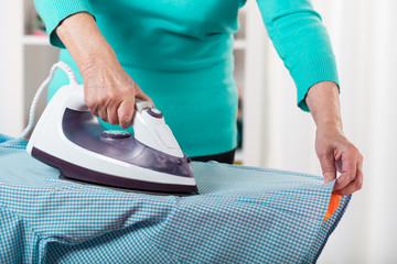 Female hands ironing a shirt