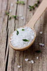 Sea salt in spoon with a fresh herbs thyme