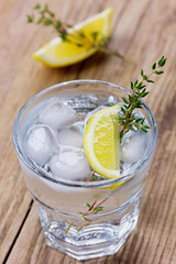 Water with lemons and ice decorated herb thyme