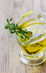 Olive oil with fresh thyme on a wooden rustic board