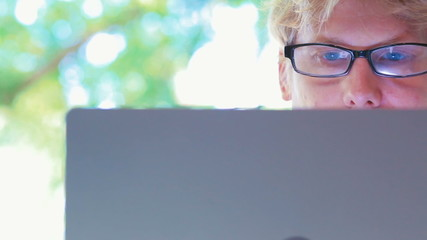 Young man with blue eyes and glasses using his laptop
