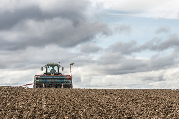 tractor seeding in a field on cloudy sky background
