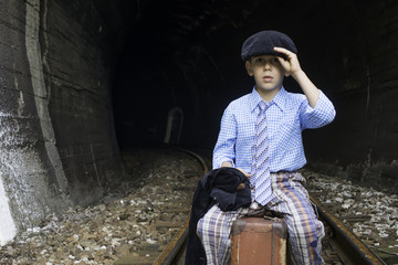 Child in vintage clothes sits on railway road