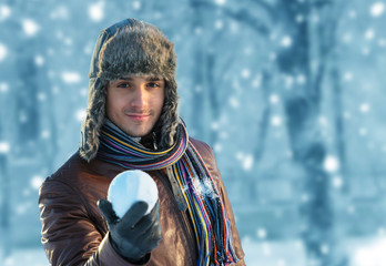 Smiling young man in ear flap hat with a snowball in his hand
