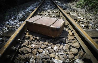 Vintage suitcase on railway road