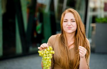 Teenager eating  grapes