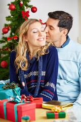 Mann küsst Frau beim Einpacken von Geschenken