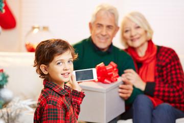 Kind macht Foto mit Handy zu Weihnachten