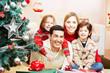 Familie zu Weihnachten mit Geschenken am Weihnachtsbaum