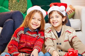 Zwei Kinder mit Weihnachtsmützen zu Weihnachten