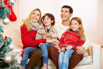Kinder sitzen bei Eltern auf dem Schoß zu Weihnachten