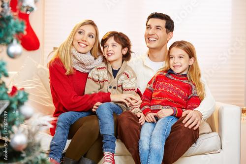 canvas print picture Kinder sitzen bei Eltern auf dem Schoß zu Weihnachten