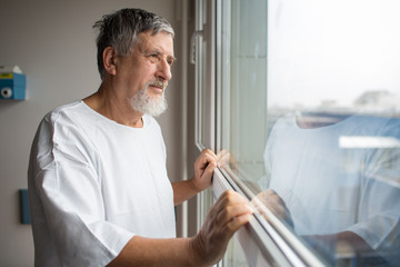 Patient at a hospital, looking from a window in his room