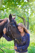 Young beautiful girl walking in the park with a horse