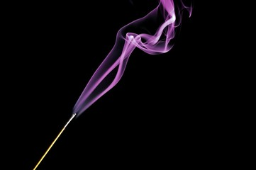 Incense stick with purple smoke isolated on black background