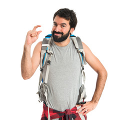 Backpacker doing tiny sign over white background