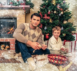Young father with his son near fireplace