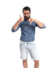Young hipster man making a good-bad sign
