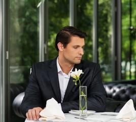 Handsome man in jacket waiting someone in restaurant
