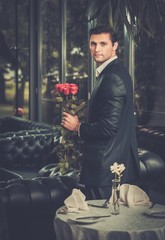 Handsome man with bunch of red roses