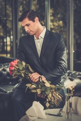 Handsome man with bunch of red roses waiting