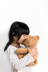 Little child kissing teddy bear